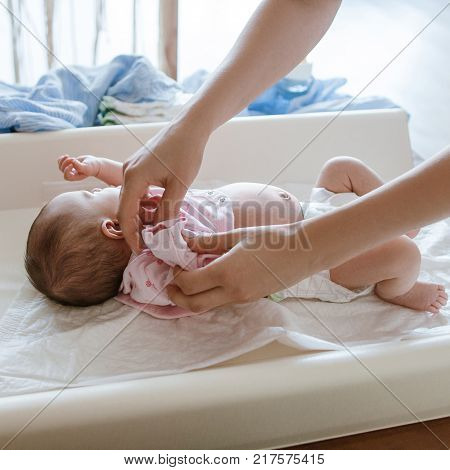 mother carefully dresses her newborn baby. happy motherhood. family lifestyle.