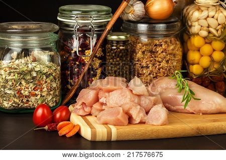 Raw chicken breast on the kitchen board. Diet food. Sale of meat. Spices for preparing meat on grill