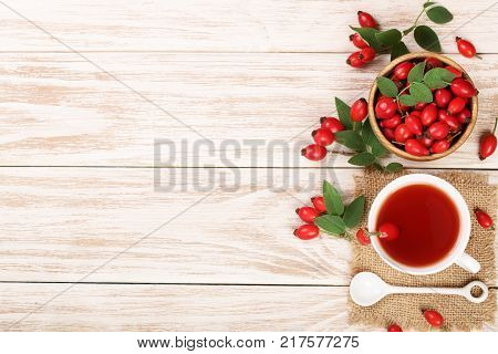 tea with rose hips and honey on a white wooden background with copy space for your text. Top view.