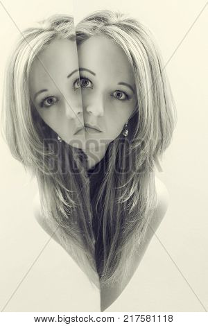 Portrait close-up of a beautiful blond woman looking around the corner of a mirror in artistic conversion