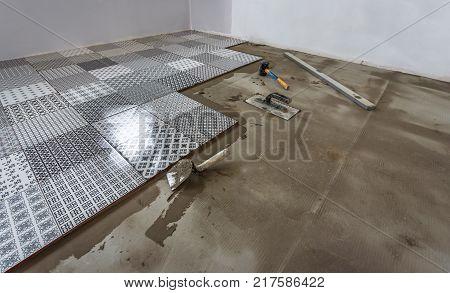 Ceramic tiles and tools for tiler. Floor tiles installation.