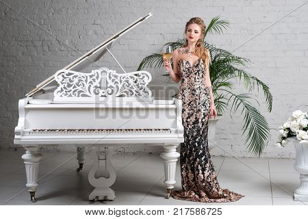 Elegant blonde lady with glass of wine in restaurant standing near white grand piano in a luxury classic interior. Beautiful sexy young woman with perfect body and pretty face make up wearing evening dress drinking alcohol in luxury interior