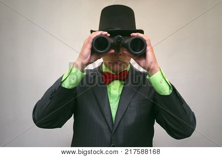 Spy. Secret detecive agent holds binoculars in his hands and looks through him isolated. Vintage gangster.