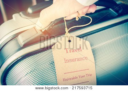 Hands holding Travel Insurance tag on Suitcase safety with letters enjoyable your trip on bag light blurred background that is intended cover medical expenses trip cancellation or flight accident.