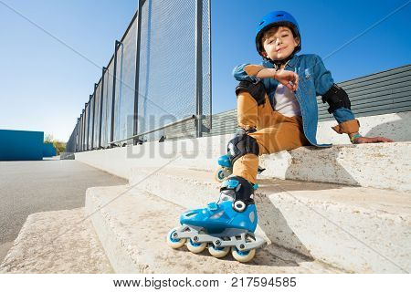 Portrait of cheerful boy wearing roller blades and protective gear, sitting on the stairs of outdoor rollerdrom