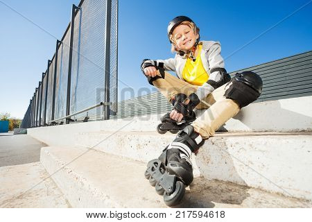 Smiling blond boy in roller blades sitting on the stairs of skate park at sunny day