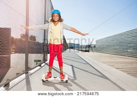 African girl in helmet riding hoverboard or electric self balancing gyro scooter board on the side walk