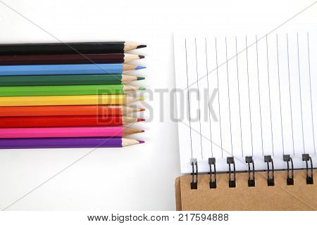 colorful pencils with spiral notebook on white table