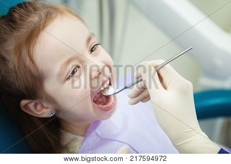 Happy child in comfortable dentist chair with paper napkin on chest and doctor in rubber gloves who checks mouth with sharp metal instrument and magnifying glass.