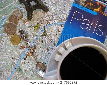 Symbols of Paris and France in flat layout or background. Cup of coffee with sugar, Eiffel tower, tea spoon, guide to Paris with map, old French coins francs and centimes. Vacation tour or tourist journey to Europe. Editorial only. The map used in composi
