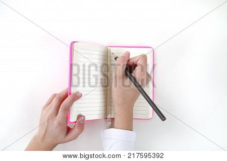 young woman writing in a pink notebook