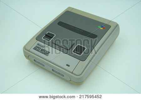 Almere, Netherlands-  December 9, 2017: Classic Super Nintendo (SNES) video game console deck against a white background.  The 16-bit SNES is was one of the most popular game consoles during the '90s.
