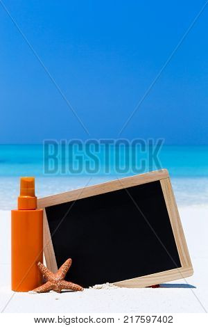 Sunscreen lotion in orange tube with chalk board decorated star fish on sandy beach. Skin care concept card with sea background.