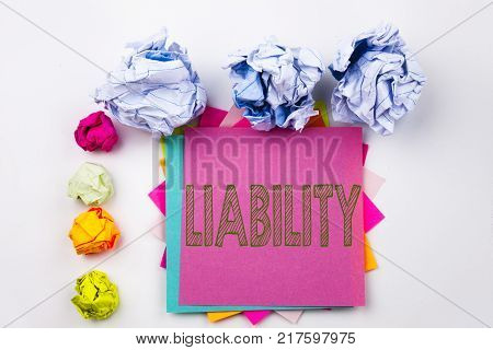 Writing text showing Liability written on sticky note in office with screw paper balls. Business concept for Accountability Legal Blame Risk on white isolated background.