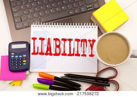 Word writing Liability in the office with  laptop, marker, pen, stationery, coffee. Business concept for Accountability Legal Blame Risk Workshop white background with space