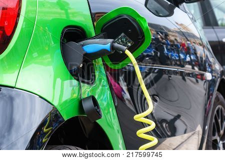 Close up of the power supply plugged into an electric car being charged.