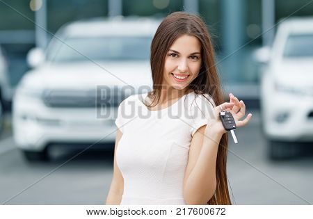 Happy woman driver showing car keys and leaning
