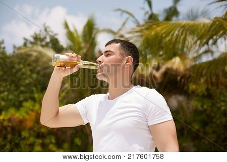 Young man drinking beer on the tropical beach with coconut palm trees on background. Male with a bottle of lemonade beverage quenches thirst.