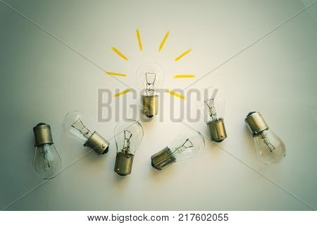 Light bulb with rays on a white background. Concept- idea innovation business concept creativity inspiration. Toned.
