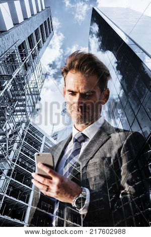 double exposure picture of a businessman with phone and skyscrapers with construction sites
