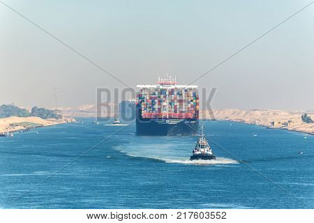 Ismailia Egypt - November 5 2017: Large container vessel ship MSC Maya passing Suez Canal in the sandy haze in Egypt. Tugboat accompanies the ships.