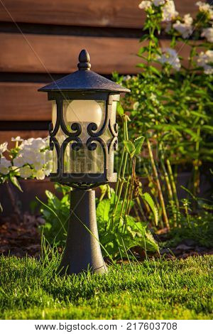 garden lamp, made in the Middle Ages, on a lawn with a juicy green grass.