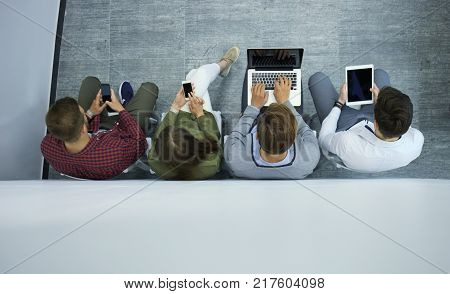 Group of attractive young people sitting on the floor using a laptop, Tablet PC, smart phones, smiling