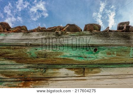 Vintage wooden roof with red tiles and eaves detail under blue skies with white fluffy clouds