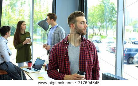 Happy attracive young businessman drinking coffee in office