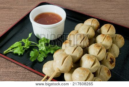 Food and Cuisine Grilled Meatballs on Wooden Skewer Served with Spicy Sauce.
