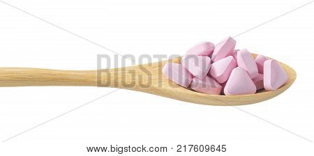 Healthcare Concept A Wooden Spoon Full with Pink Vitamins Pills isolated on White Background.