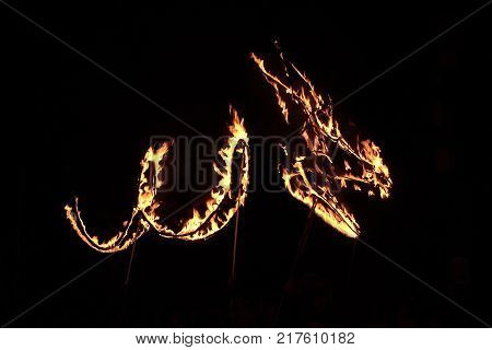 Dragon silhouette in fire during a fire show in the dark night. Dragon in fire isolated on black background.
