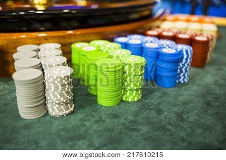 Colourful roulette chips in a casino on a gambling table. Lots of chips with different nomination and colours.