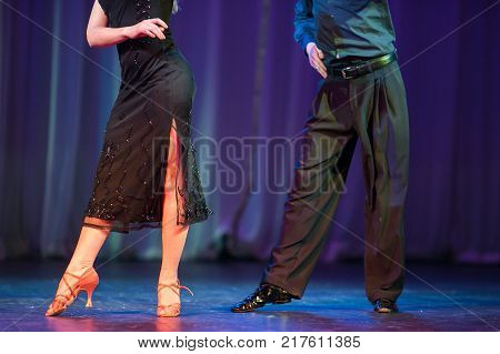 performance, costume design, dance concept. elegant legs of dancing woman nearby with her partner legs in trousers, they are dancing latino american dances on the stage of the theater