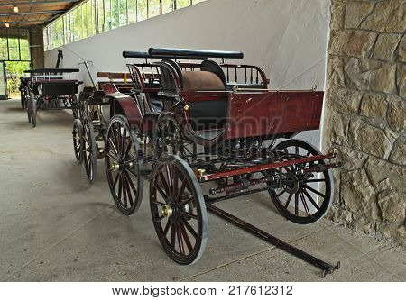 Several vintage old style chariots in barn