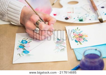 handcrafting, painting, hobby concept. close up of female arm that is holding thin brush and drawing flowers on the heavy stock paper that is rather rough and used for greetin cards