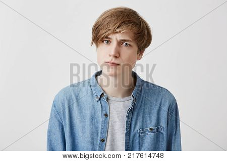 Portrait of young irritated caucasian male with fair hair and blue eyes looks with anger at camera, dissatisfied hear some comments, tries to control emotions and not speak out his mind in presence of many people and guests