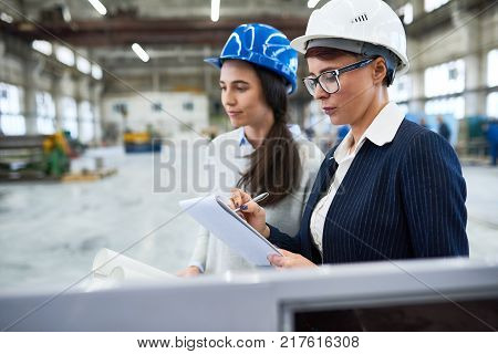 Carrying out inspection at modern plant: group of confident inspectors wearing hardhats standing at production department and taking necessary notes