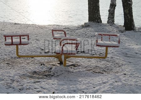 lost metal merry-go-round covered shine snow on the sea shore