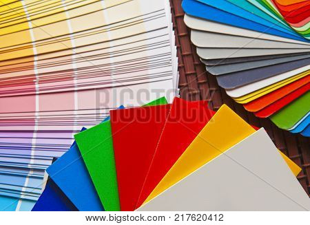 Set of open Pantone/RAL color cards on bamboo mat