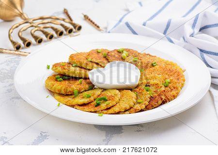 Traditional Hanukkah dish latkes - potato pancakes with sour cream with