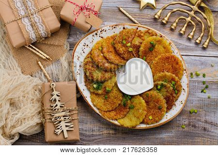 Traditional Hanukkah dish latkes - potato pancakes with sour cream. Table decorated with menorah, gift boxes and candles