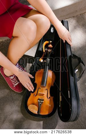 classical music instrument. woman takes violin out of a case to perform in the street. art hobby making money concept