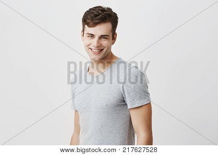 Positive european guy with blue eyes dressed casually having pleasant smile showing his perfect white teeth having good mood after party and meeting with his friends. Cheerful good-looking male model posing against gray background.