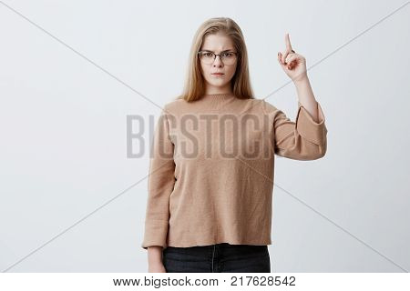 Studio picture of angry and indignant young caucasian female with blonde hair and eyeglasses looking up and pointing index finger upwards, feeling irritated with noise coming from neighbors above. Body language