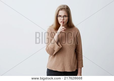 Angry annoyed casually dressed blonde female in eyeglasses keeping index finger on her lips, saying shh, asking for silence and privacy, irritated with loud music or noise. Negative human emotions and feelings