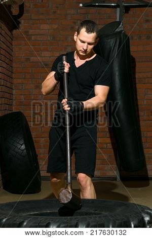 sport exercises with a large auto wheel and a sledgehammer against a brick wall background