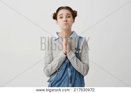 Woman with brown hair in double buns posing on camera with pity look holding hands in praying. Pathetic emotions of girl asking for forgiveness over white background. Concept of emotions