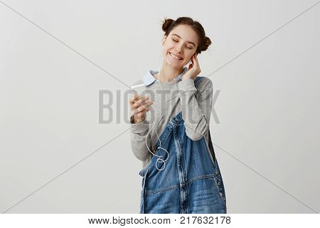 Portrait of glad delighted girl putting earphones taking enjoying merriment alone with music. Cute woman closing eyes in pleasure after getting compliments from husband. Human emotions