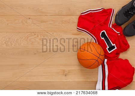Basketball player outfit background top view, copy space. Professional uniform, ball and sneakers on parquet floor